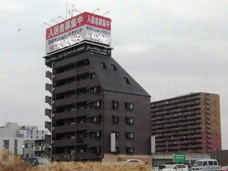 万博記念公園駅近くの賃貸マンションの屋上にある広告看板を何とかしてほしい!